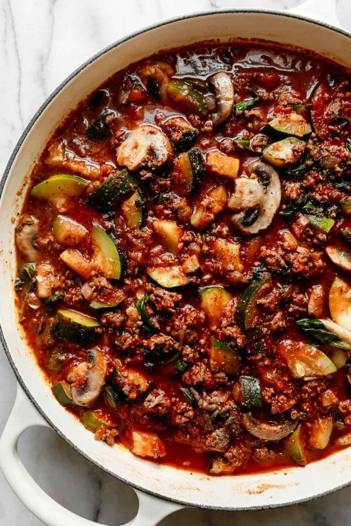 Overhead view of the beef and veggie filling for one-skillet zucchini lasagna in white skillet