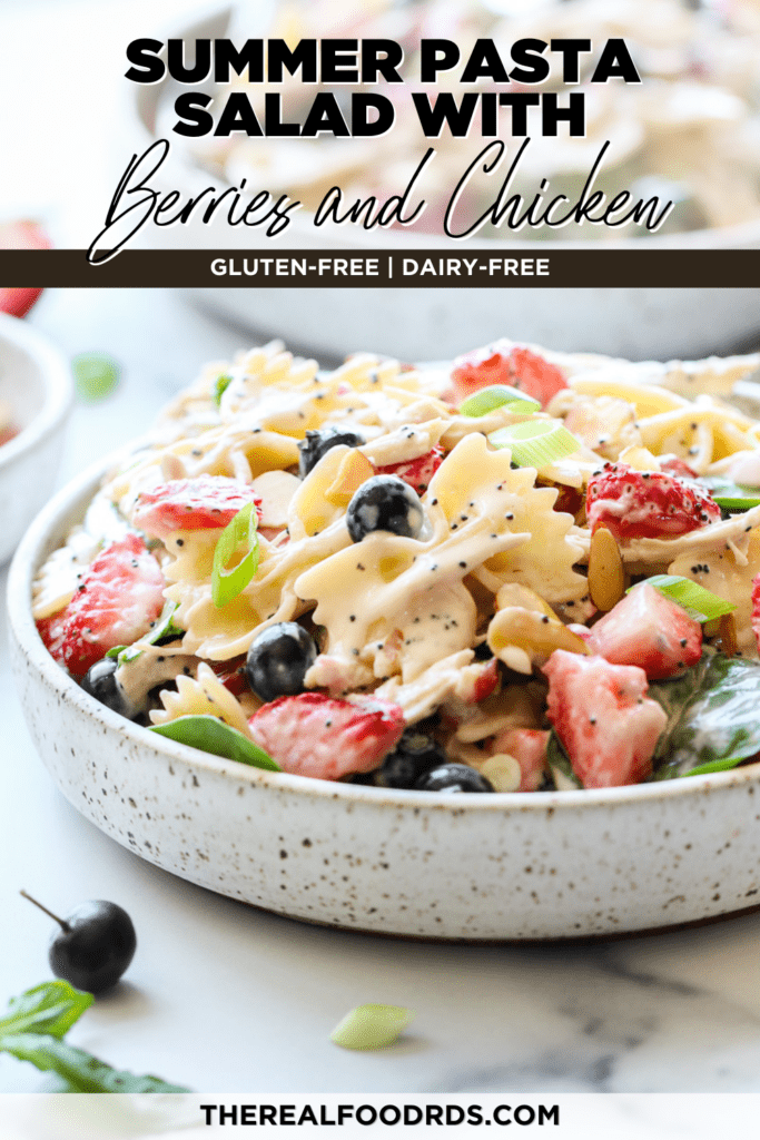 Creamy pasta salad with fresh berries and chicken in a speckled bowl topped with poppy seed dressing