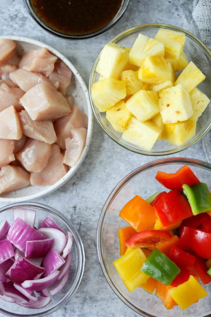 All ingredients for teriyaki chicken pineapple kebabs in glass bowls