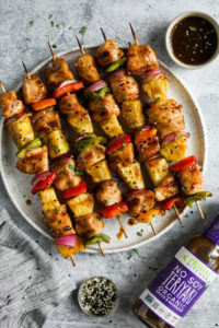 Teriyaki chicken kebabs with pineapple and peppers on skewers plated ready for serving