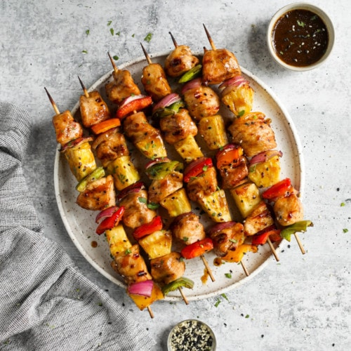 Grilled teriyaki chicken pineapple kebabs lined up on a speckled plate