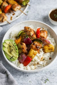 Teriyaki chicken with pineapple and peppers served over rice plated on a speckled plate with sliced avocado on the side