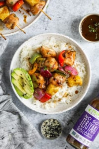 Grilled chicken kebabs with pineapple, peppers, and red onion over rice with a side of sliced avocado plated