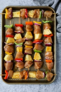Pineapple chicken kebabs on skewers lined up on a baking sheet ready for the grill