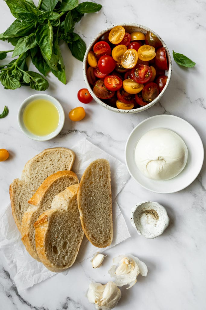 All ingredients for easy skillet bruschetta with burrata arranged together on a marble countertop