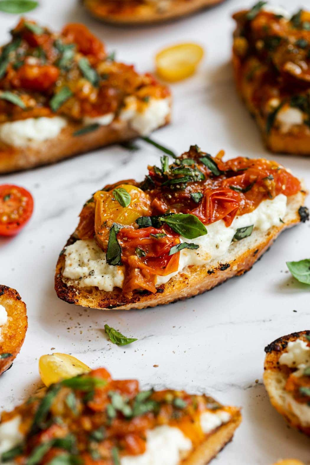 Freshly made bruschetta on crusty bread and topped with burrata, tomatoes, and fresh basil