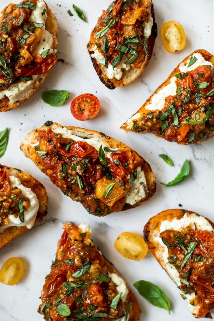 Several slices of bruschetta topped with burrata and sautéed tomatoes on a countertop