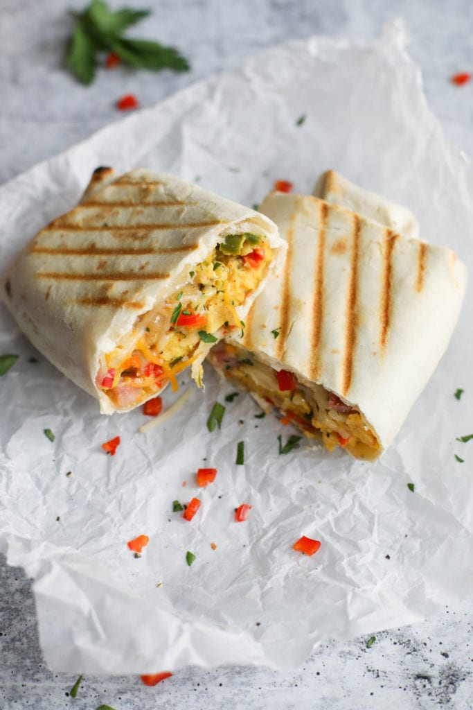 An omelet and ham filled freezer breakfast burrito cut in half with grill marks on the tortilla