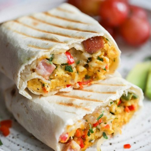 A breakfast burrito filled with scrambled eggs and ham cut in half with grill marks on the tortilla.
