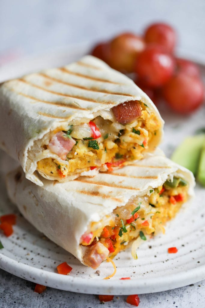A freezer omelet burrito cut in half, stack on top of each other, with grill marks on the tortilla and melty cheese mixed with ham and scrambled egg for the filling.