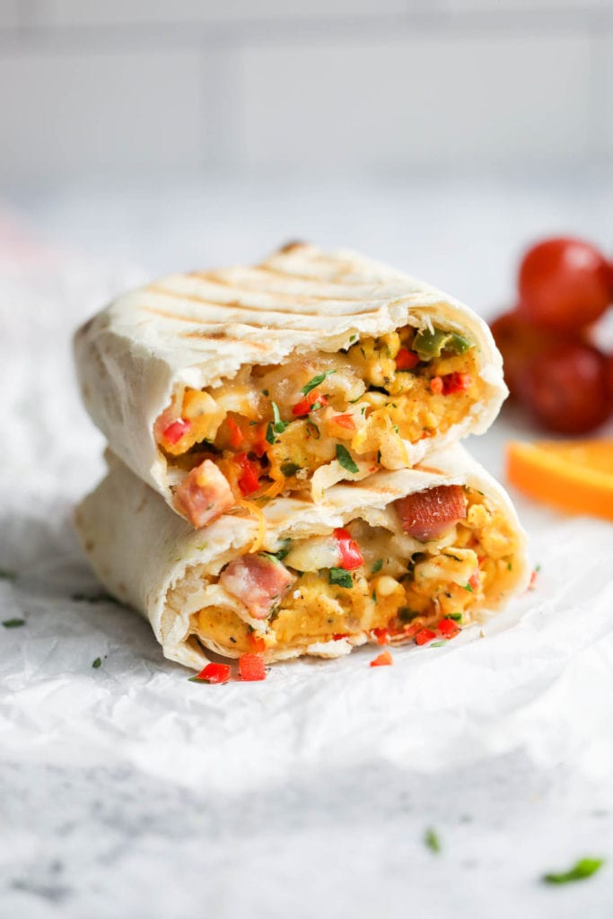 An omelet filled breakfast burrito cut in half, stacked on top of each other, with grill marks on the tortilla.