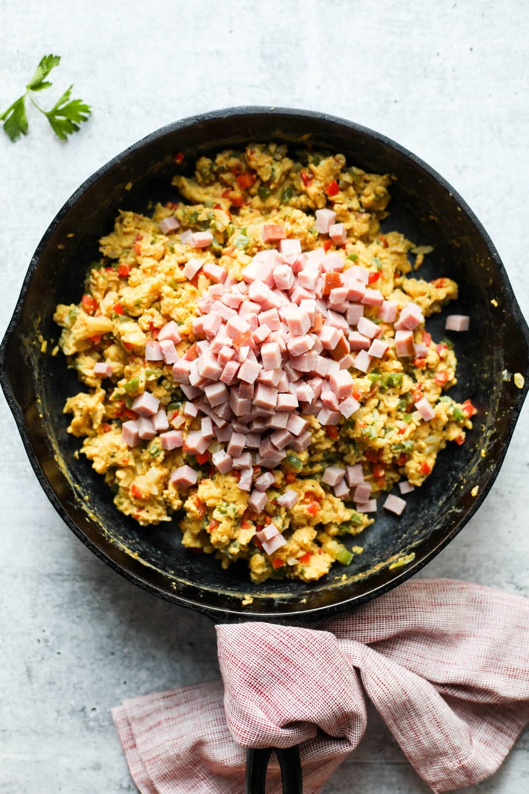 Overhead view of scrambled eggs in a cast iron skillet with diced ham added to the top