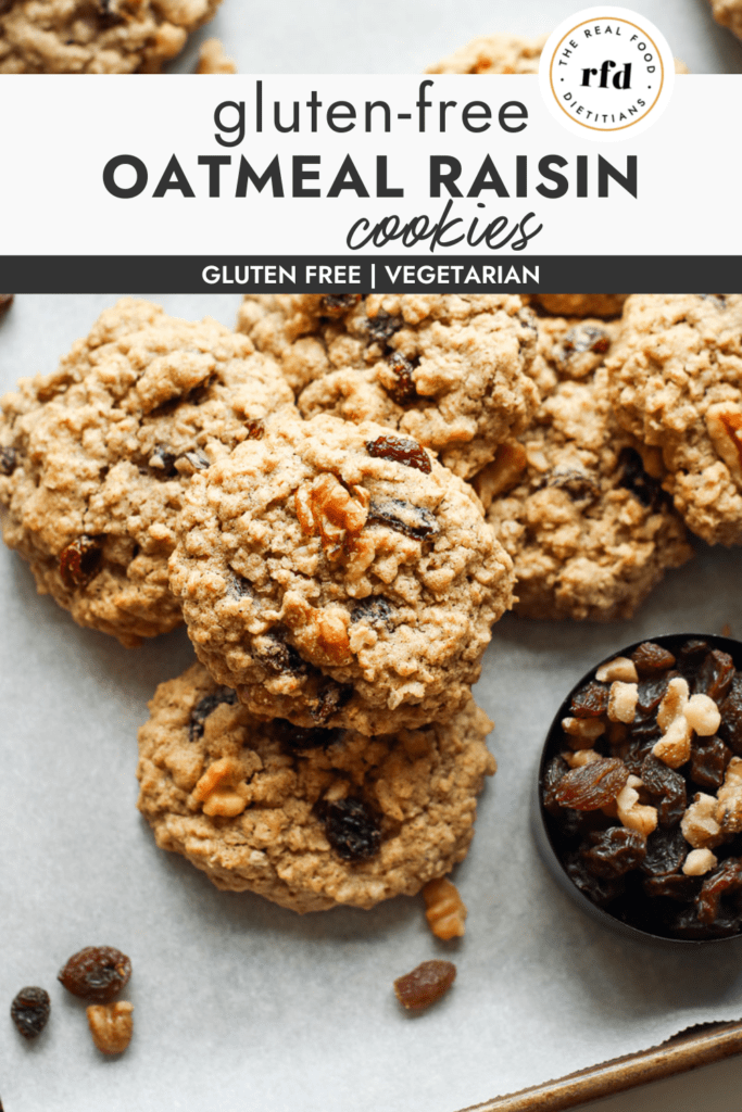A pile of oatmeal raisin cookies on a parchment covered baking sheet made gluten-free topped with walnuts