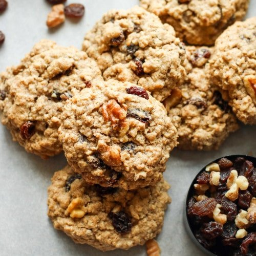 A pile of oatmeal raisin cookies topped with walnuts