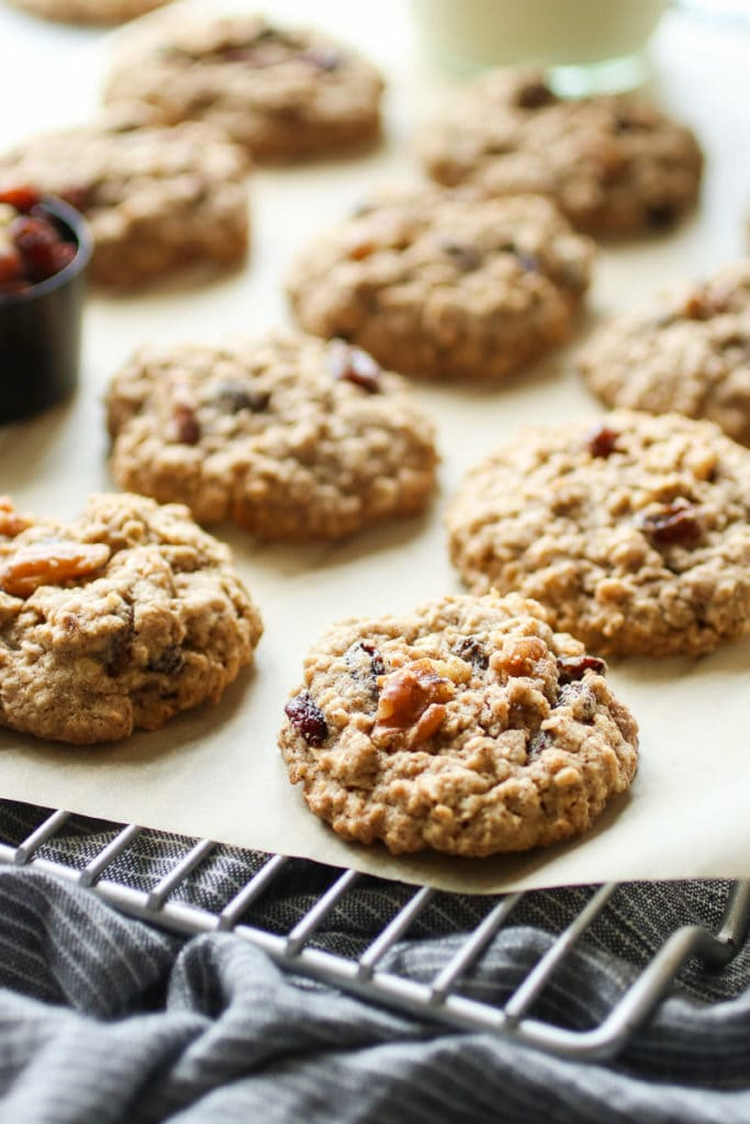 Oatmeal raisin cookies lined up on a parchment lined cooling rack and topped with extra walnuts.
