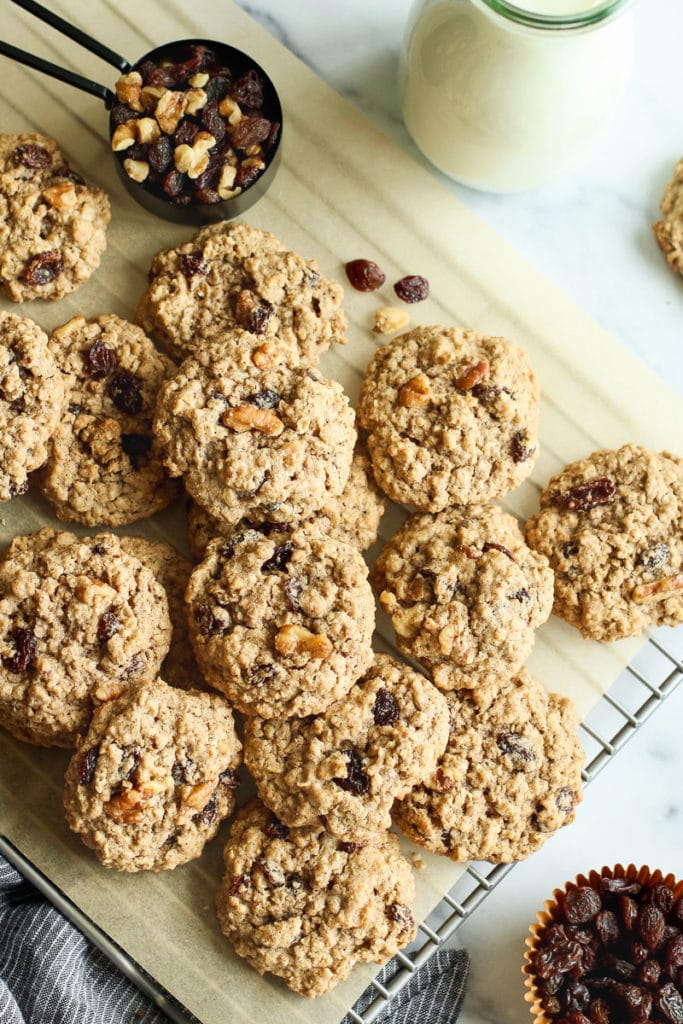 A pile of gluten-free oatmeal raisin cookies on a parchment covered cooling rack with a measuring cup filled with extra raisins and walnuts.