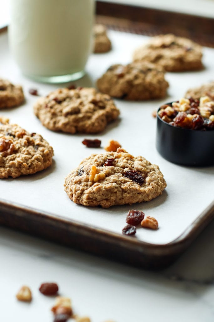 Oatmeal raisin cookies on a parchment covered baking sheet topped with extra walnuts and raisins.