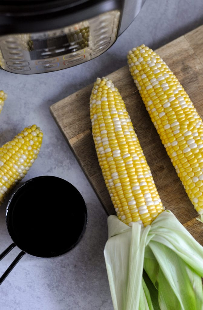 Overhead view of corn on the cob with the green husk pulled down to the end laying on a cutting board next to an Instant Pot and black measuring cup filled with water