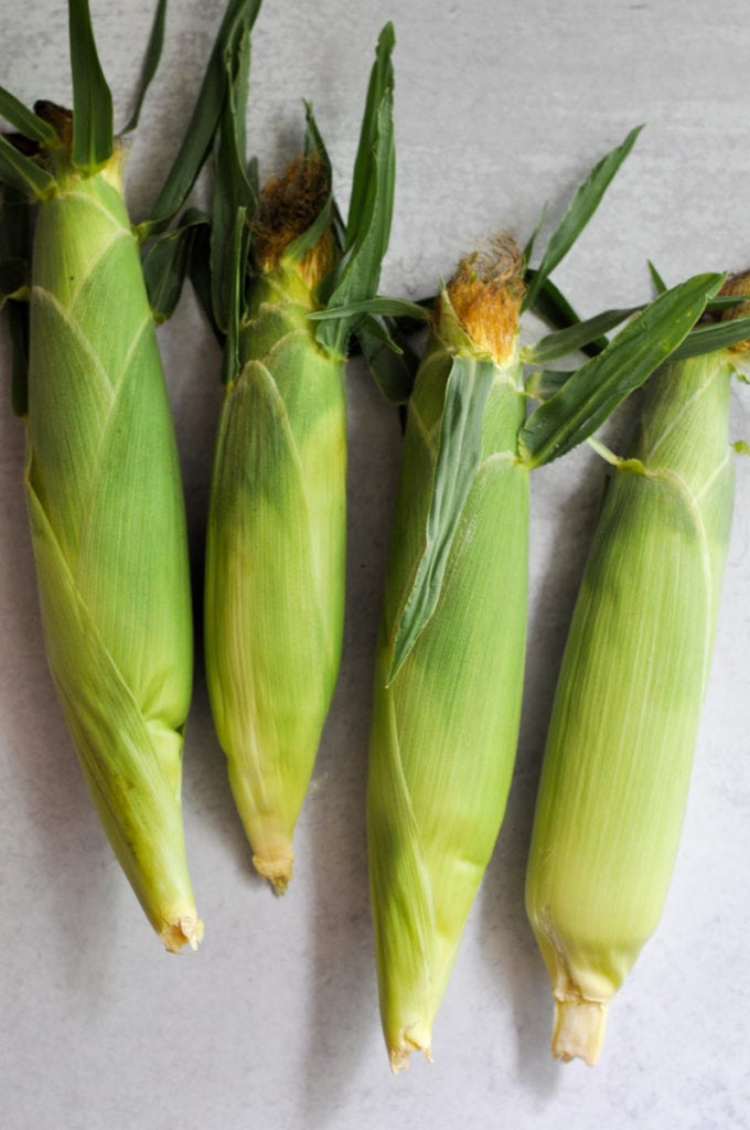 Four ears of corn still in the husk laying on the counter