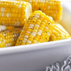Corn on the cob made in the Instant Pot in a white serving dish with cracked black pepper sprinkled on top