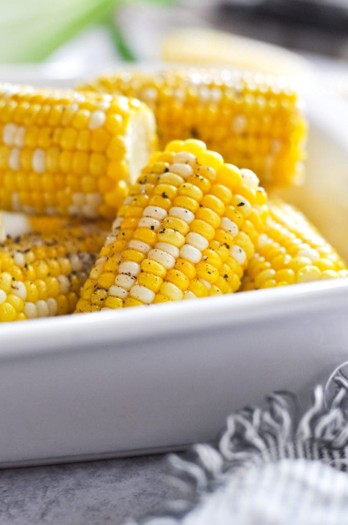 Golden yellow corn on the cob halves in a white serving dish sprinkled with cracked black pepper