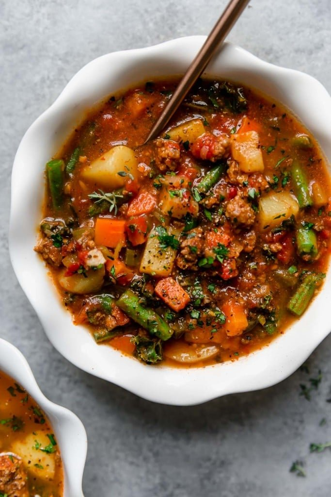 Overhead view of slow cooker healthy hamburger soup topped with fresh herbs.