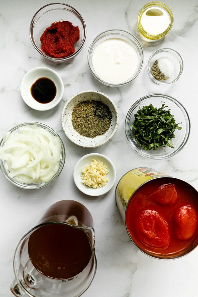All ingredients for creamy tomato basil soup in small bowls arranged on a marbled countertop.