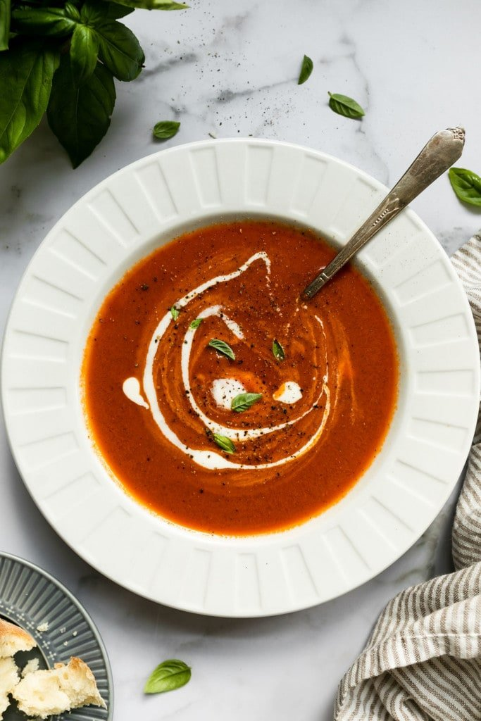 Creamy tomato basil soup in a white bowl with a swirl of cream going through the middle.