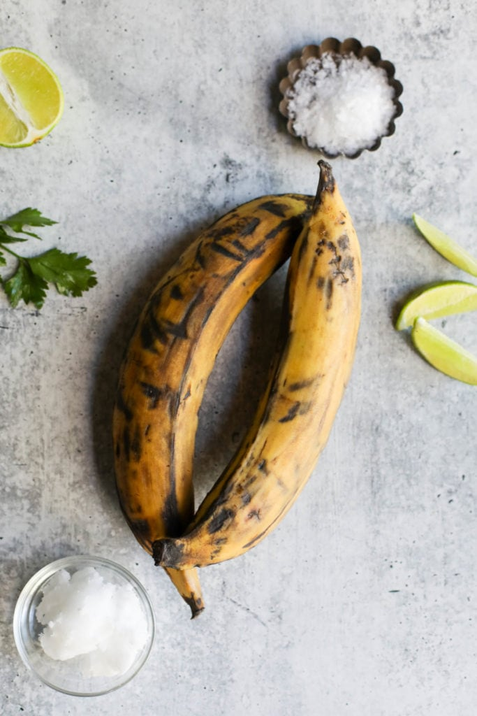 Two overripe plantains with dark spots on a grey countertop with limes and a bowl of coconut oil and sea salt off to the side preparing to make fried plantains.