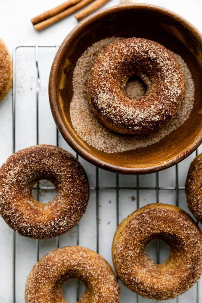 Cinnamon sugar baked donuts on a cooling rack with one donut in a bowl of cinnamon sugar to be coated.