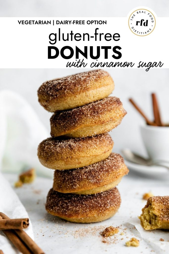 A tall stack of gluten-free baked donuts coated in cinnamon sugar.