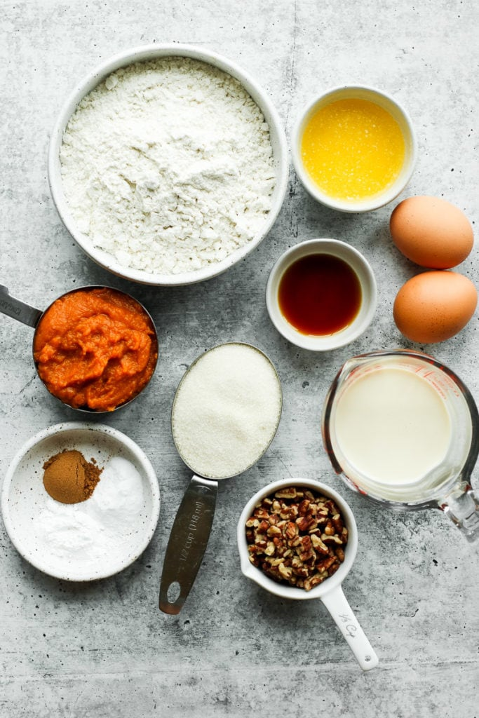 All ingredients for pumpkin coffee cake in a grouping on a grey and white countertop.