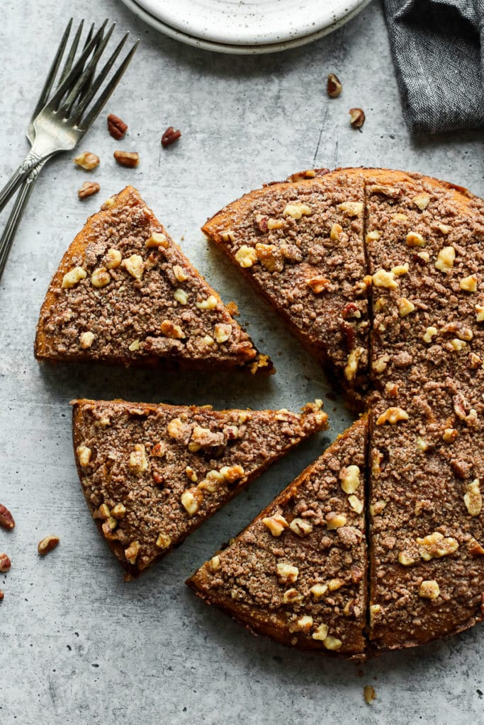 A round pumpkin coffee cake topped with crumble and pecans cut in half with slices.