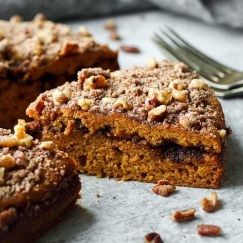 A thick slice of gluten-free pumpkin coffee cake with a cinnamon pecan swirl in the middle layer.