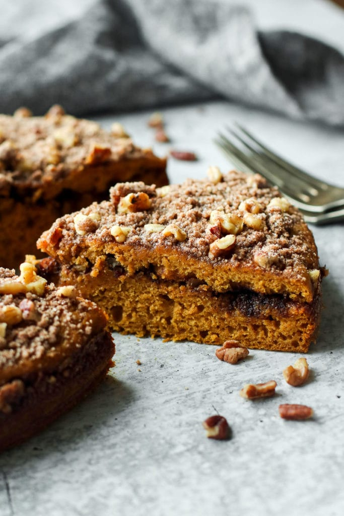 A close up view of gluten-free pumpkin coffee cake with a cinnamon swirl middle layer and topped with cinnamon crumble and pecans.