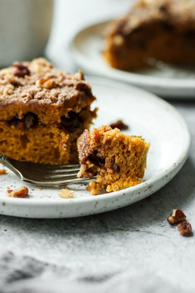 A fork full of fluffy and moist gluten-free pumpkin coffee cake on a speckled plate.