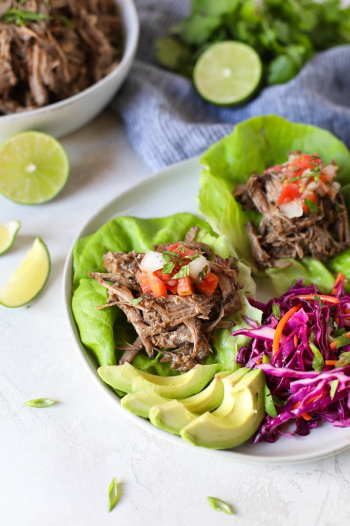 Overhead view of shredded Slow Cooker Beer Barbacoa in lettuce wraps. Part of our Healthy Crockpot Recipes Roundup.