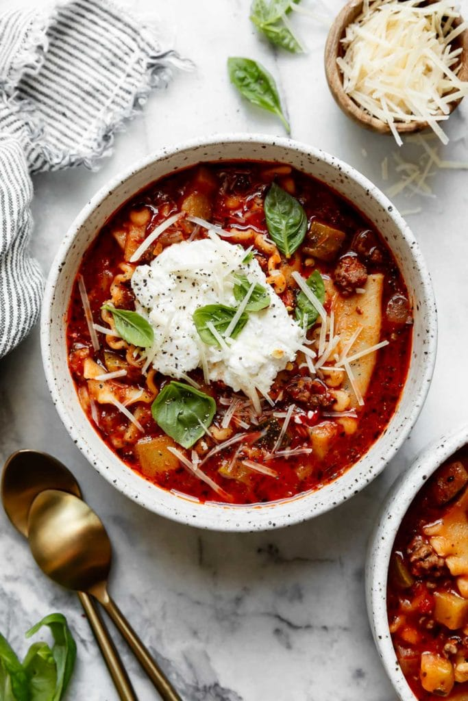 An overhead view of Instant Pot Lasagna Soup in a speckled bowl topped with ricotta cheese, fresh basil, and fresh parmesan cheese.