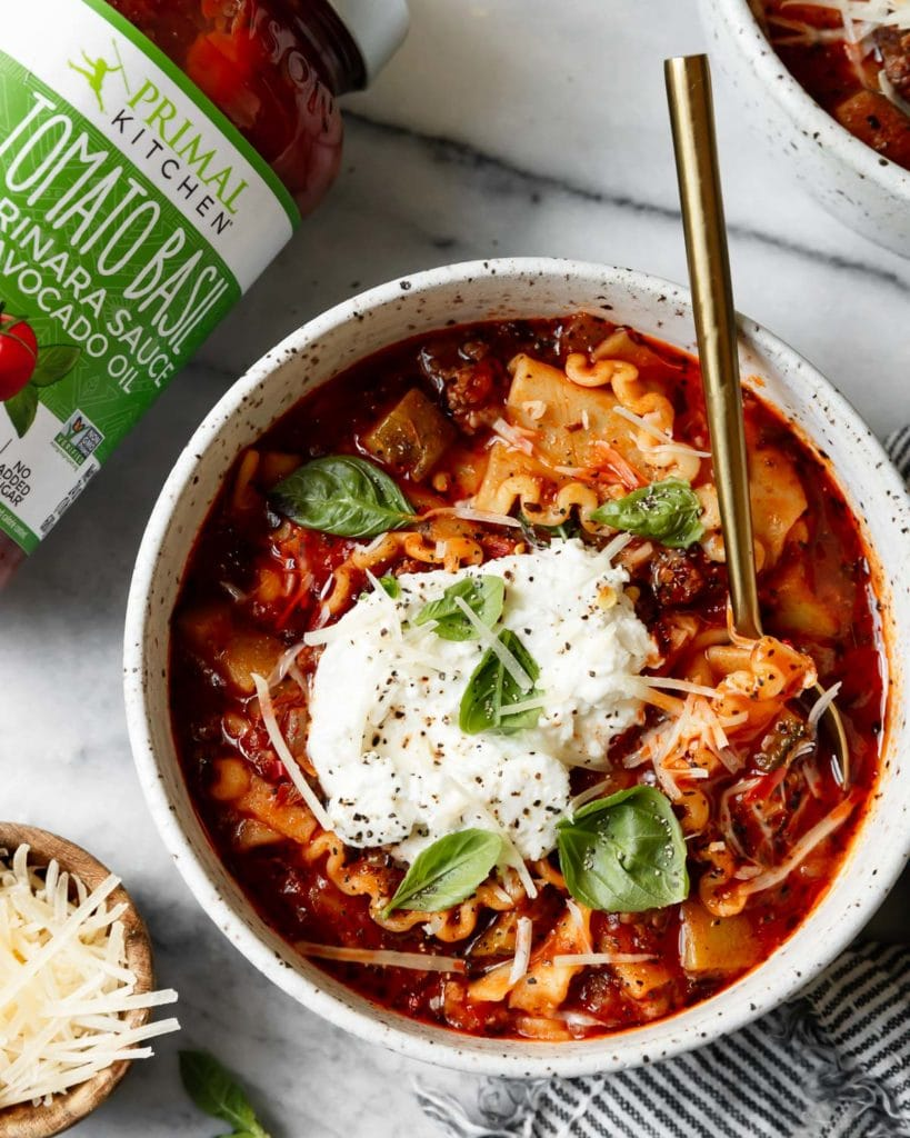 Creamy lasagna soup made with gluten-free lasagna noodles, ground beef, and marinara sauce from Primal Kitchen in a bowl with a gold spoon.