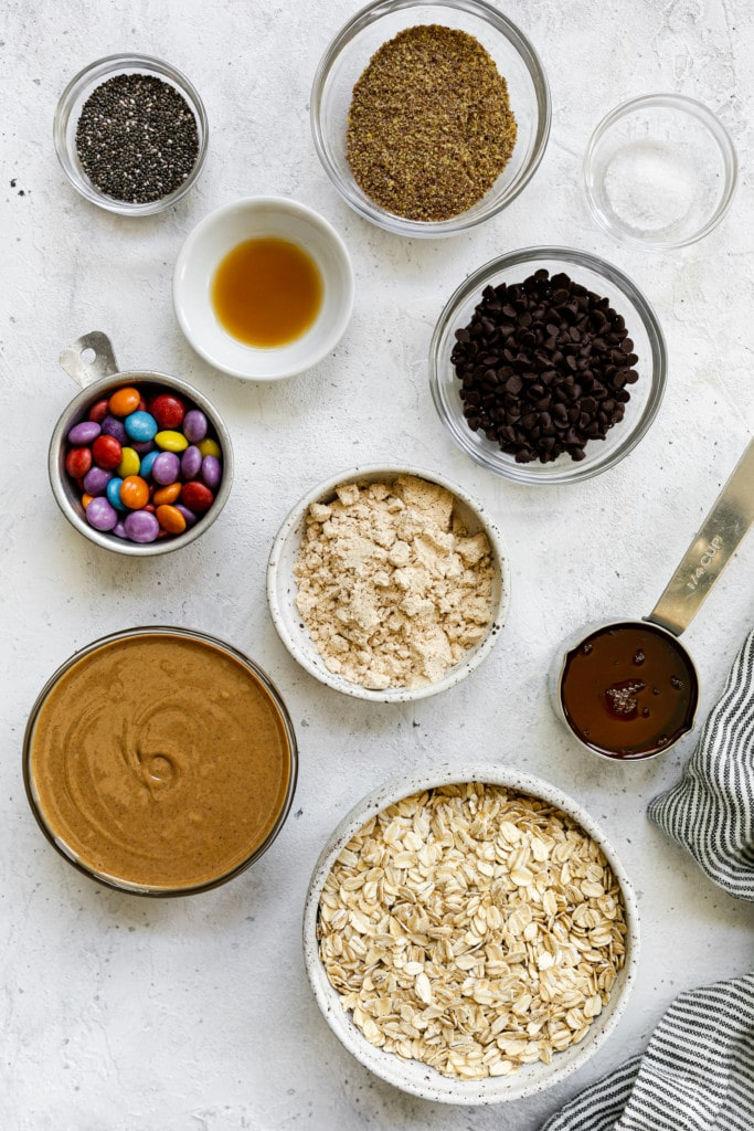 All ingredients for monster cookie peanut butter protein bites in small bowls and measuring cups on a countertop in an overhead shot.