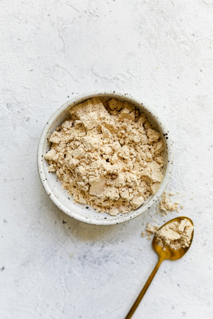 Whey protein powder in a speckled bowl with a spoonful of whey powder on a gold spoon.