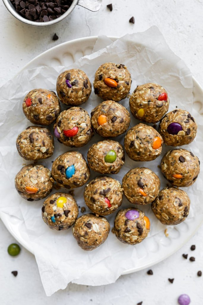Overhead view of monster cookie peanut butter protein balls with colorful candy coated chocolate pieces in each ball. Plated on a parchment covered plate.