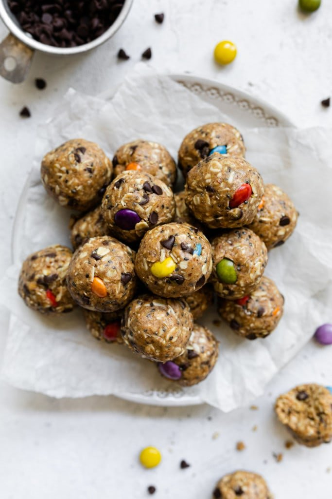 Monster Cookie Peanut Butter Protein Balls perfectly rolled into balls with colorful candy-coated chocolate pieces in each ball, all stacked up in a large pile.