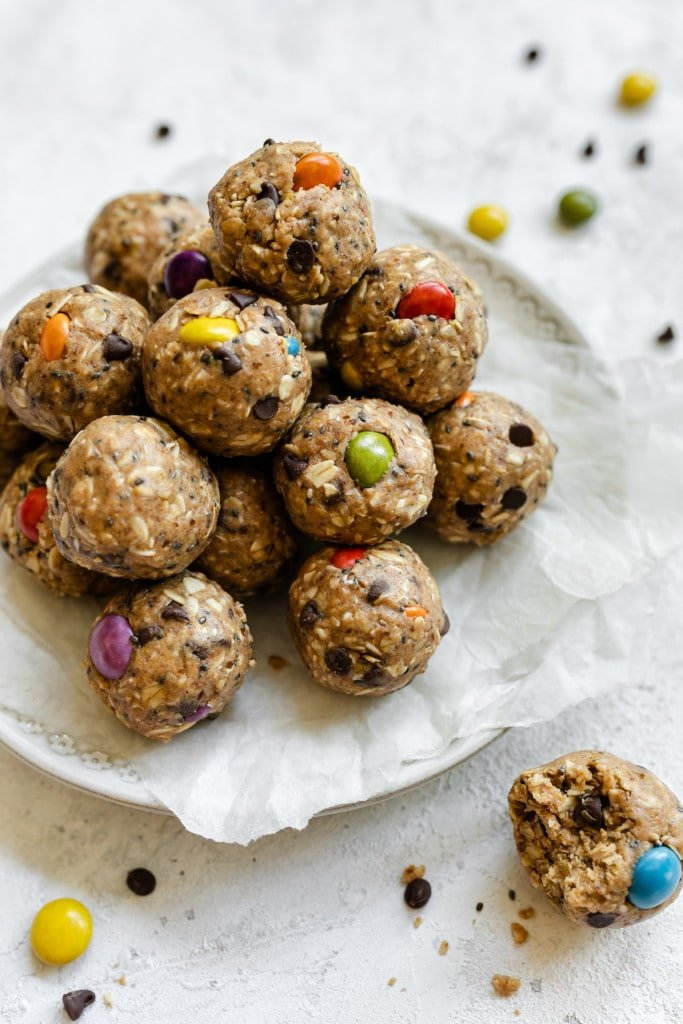A pyramid stack of monster cookie peanut butter protein balls on a parchment covered plate.