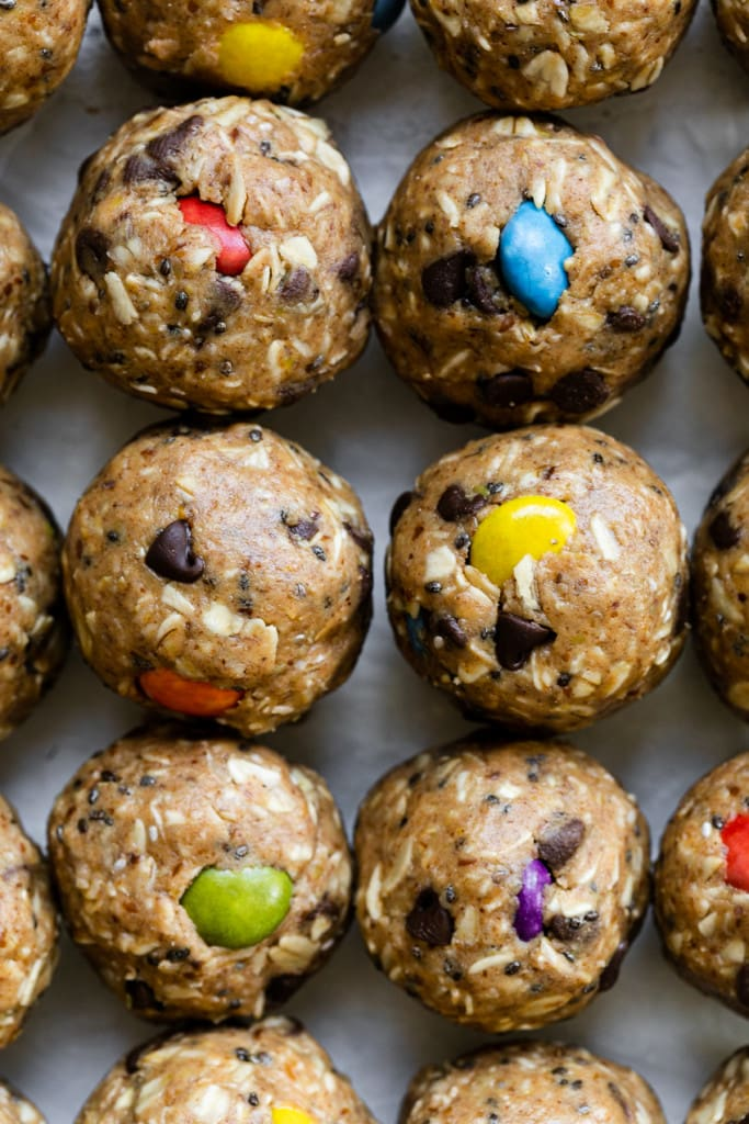 A close up shot of monster cookie peanut butter balls lined up on a piece of parchment paper with colorful candy-coated chocolate pieces in each ball.