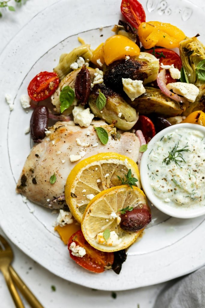 A close up view of roasted Greek veggies, artichoke, tomatoes, kalamata olives, on a plate with a roasted chicken thigh and a side of Tzatziki sauce.