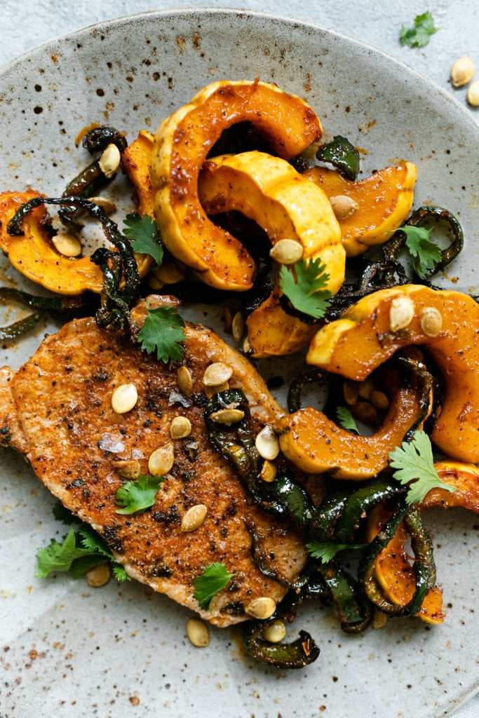 A close up of oven baked pork chops with a side of roasted delicata squash and poblano peppers topped with roasted delicata squash seeds drizzled with a glaze.