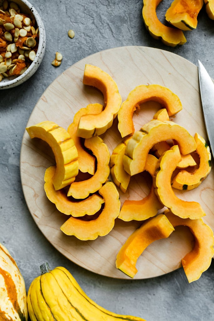 Delicata squash cut into strips laying on a cutting board ready for roasting.