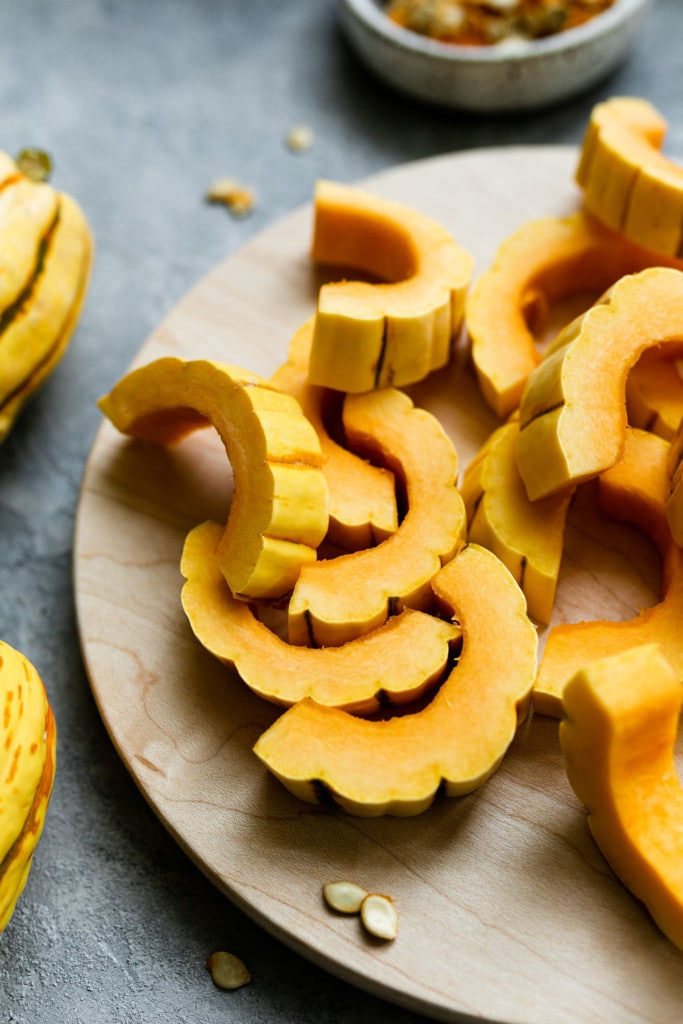 Delicata squash cut into strips laying on a cutting board ready for roasting in the oven.
