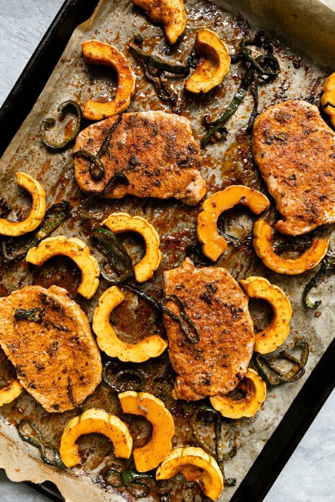 Overhead view of seasoned pork chops on a sheet pan with poblano peppers and delicata squash.